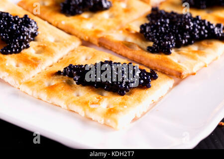 Caviar over crackers in a tray, horizontal image - Stock Photo