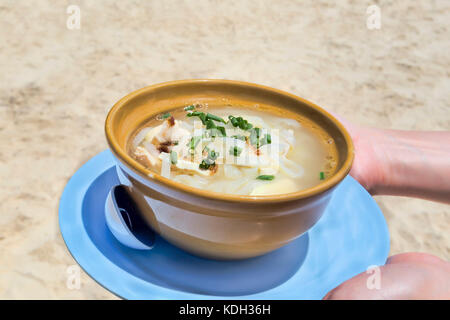 Thai chicken noodle soup on the beach - selective focus - Stock Photo