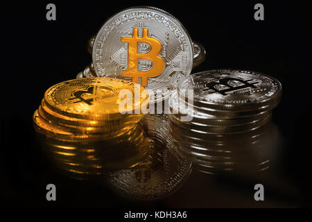 Golden and silver bitcoins on black background. Bitcoin is cryptocurrency - Stock Photo