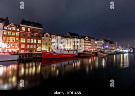 Scenic summer view of Nyhavn pier with color buildings, ships, yachts and other boats in the Old Town of Copenhagen, - Stock Photo