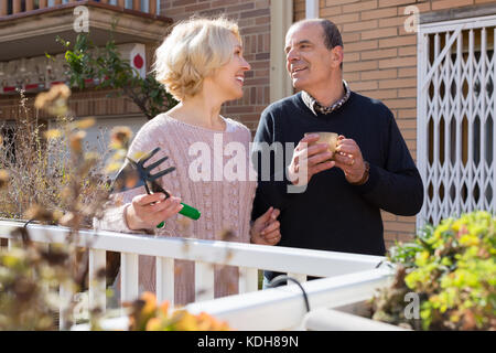 Smiling elderly woman with horticultural sundry and aged man drinking tea in patio - Stock Photo