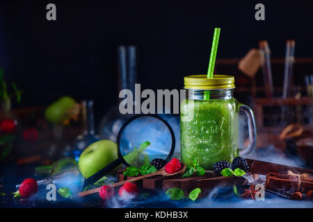 Smoothie jar with green helthy drink in a still life with berries, cinnamon, anise, magnifying glass and nutrition - Stock Photo