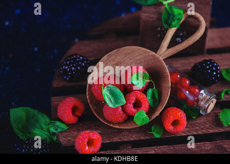 Assorted berries in a handmaiden wooden plate. Raspberry and blackberry with green mint leaves. Dark food photography - Stock Photo