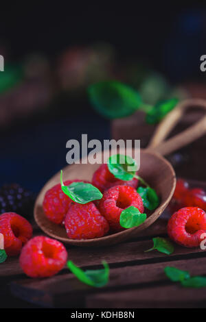Summer still life with berries in a wide wooden spoon on a dark background. Raspberry with green mint leaves. - Stock Photo