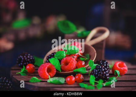 Summer still life with berries in a wide wooden spoon on a dark background. Raspberry and blackberry with green - Stock Photo