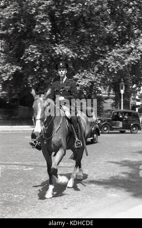 1950s, historical picture of a mounted policeman on horseback, with a London taxi in the background. - Stock Photo