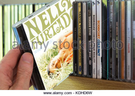Whoa Nelly , Nelly Furtado CD being chosen from a shelf of other CD's, Dorset, England - Stock Photo