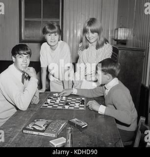 1960s, historical, four young people in a village hall, with the two boys sitting at a table playing a board game - Stock Photo