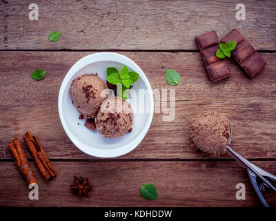 Chocolate ice cream in white bowl with fresh peppermint leaves and dark chocolate bars setup on shabby wooden background - Stock Photo
