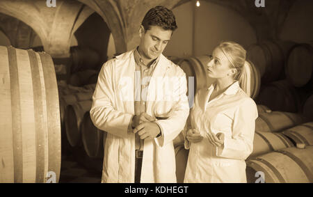 Two speaking wine house workers checking quality of product in cellar - Stock Photo