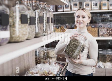 Positive young woman standing next to jars with dried herbs and picking selected in organic store - Stock Photo