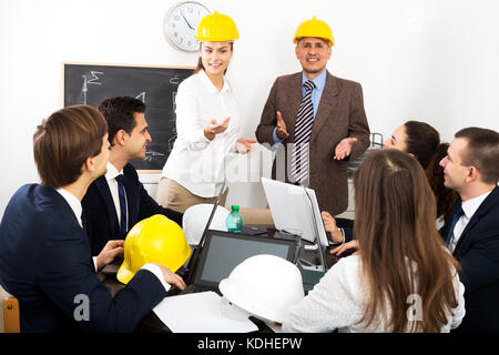Positive professionals with laptops and helmets having presentation of new project in the office - Stock Photo