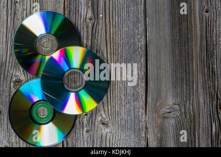 Three CD disk on dark old wooden table. Top view. Wood texture - Stock Photo
