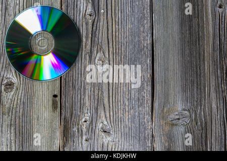 CD disk on dark wooden table. Top view. Wood texture - Stock Photo
