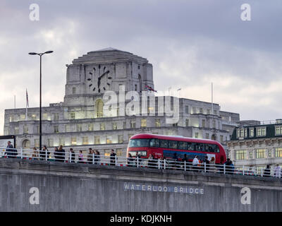 London Bus and commuters cross Waterloo Bridge in front of Shell Mex House in central London at dusk - Stock Photo