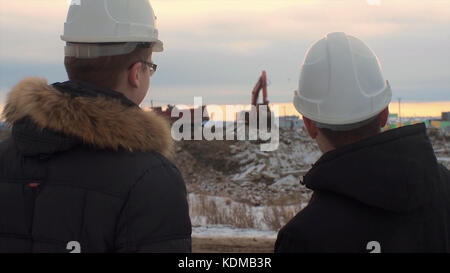 Back view of architects inspecting construction site. Two engineers in hard hats on construction site excavator - Stock Photo