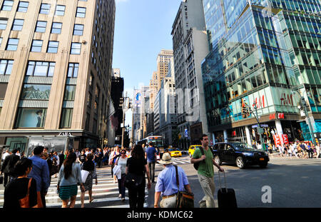 Pedestrians crossing 42nd Street along the 5th Ave in Manhattan. - Stock Photo