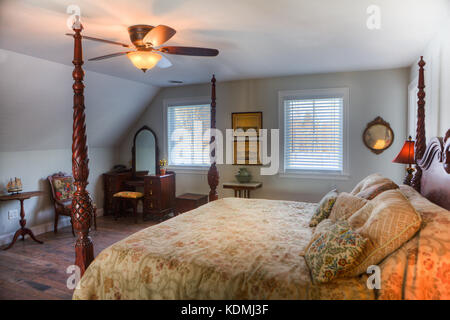 Bedroom with four-poster bed, bedside table, ceiling fan, hardwood floor and adjoining private bathroom in an upscale - Stock Photo