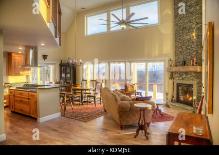 Modern, upscale living room with adjoining kitchen, dining room and stone fireplace in Vermont, USA. - Stock Photo