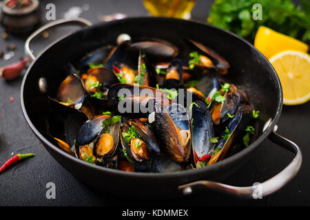 Mussels cooked in wine sauce with herbs in a frying pan on a black background. - Stock Photo
