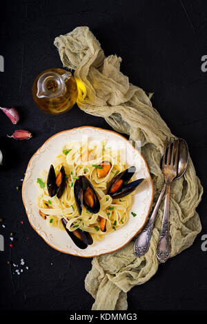 Seafood fettuccine pasta with mussels over black background. Mediterranean delicacy food. Flat lay. Top view - Stock Photo