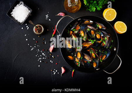 Mussels cooked in wine sauce with herbs in a frying pan on a black background. Flat lay. Top view. - Stock Photo
