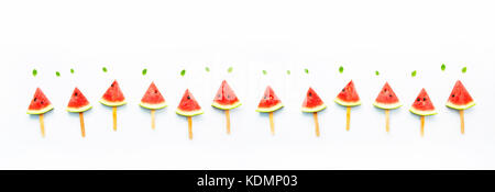 Watermelon slice popsicles and paper mint on white wooden background. - Stock Photo