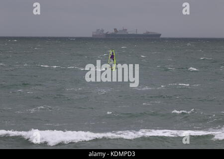 A windsurfer in rough seas off Sandown, Isle of Wight, with a big ship on the horizon in the background - Stock Photo