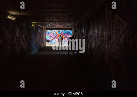 People walking through a tunnel with heavy graffitti in Prague, Europe - Stock Photo
