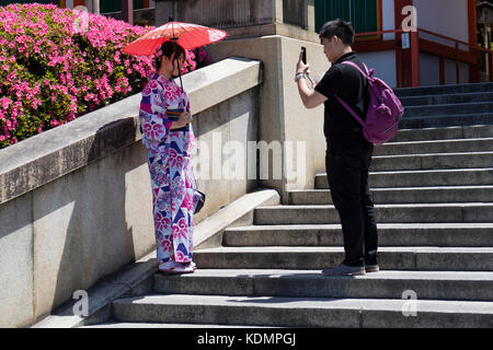 Kyoto, Japan - May 19, 2017: Traditional dressed girl in kimono with parasol is photographed at the stairs of the - Stock Photo