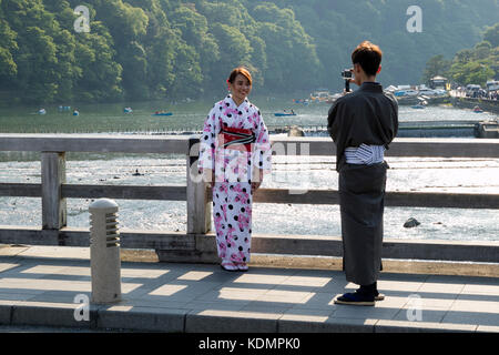 Kyoto, Japan - May 20, 2017:  Woman in kimono is phtographed on the historical Togetsukyo Bridge over the Katsura - Stock Photo