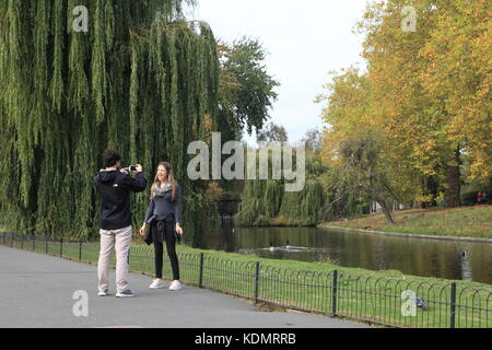 Boy takes a photo or video of a girl in Regents park.  Teenagers mucking around. - Stock Photo