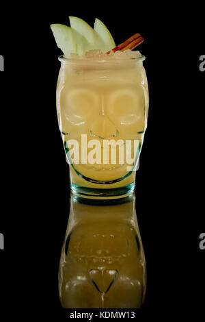 Scull glass with cocktail with orange and apple on black background with reflection - Stock Photo