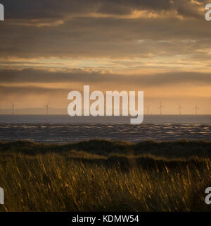 Moody evening on Formby beach looking towards Wales over the offshore wind turbines - Stock Photo