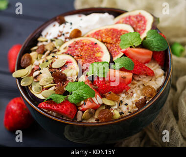 Delicious and healthy oatmeal with figs, seeds, strawberry and yogurt. Healthy breakfast. Fitness food. Proper nutrition. - Stock Photo
