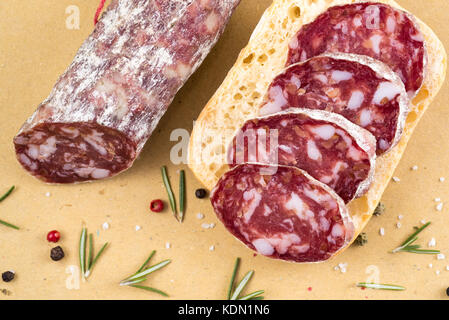 slices of italian salami on bread and some spices - Stock Photo
