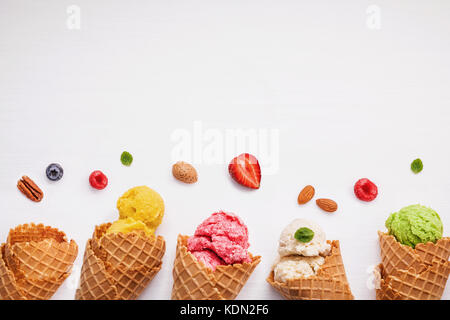 Colorful ice cream with cones and various fruits raspberry ,blueberry ,strawberry ,almonds and peppermint leaves - Stock Photo