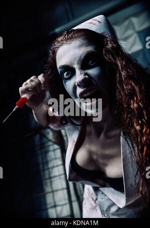 Horror shot: the crazy evil nurse (doctor) with syringe in hand. Zombie woman (living dead) - Stock Photo