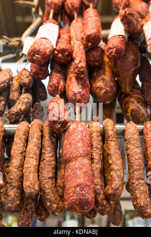 Salami, pepperoni and assorted cured dried meats hanging in Italian market - Stock Photo