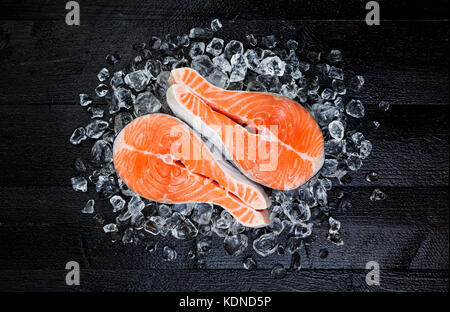 Salmon steak on ice on black wooden table top view - Stock Photo