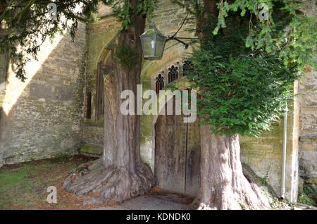 North door flanked by yew trees, St Edward's Parish Church, Stow-on-the-Wold, in the Cotswolds, United Kingdom - Stock Photo