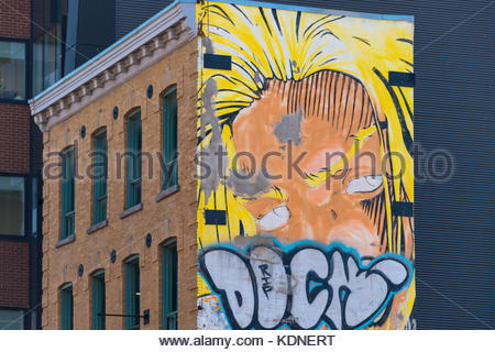 Urban graffiti painted in an old red brick building part of the city heritage. - Stock Photo
