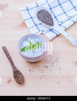 Nutritious chia seeds in ceramic bowl with wooden spoon for diet food ingredients setup on wooden background . shallow - Stock Photo