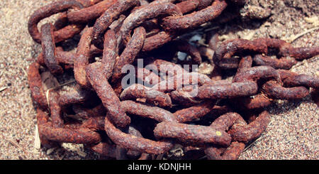 Old rustic chain on the beach. Aged photo. Wide. Unnecessary boat equipment in the pile. Wide photo for site slider. - Stock Photo