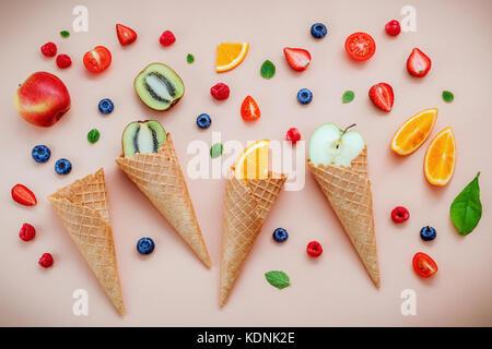 Cones and colorful various fruits raspberry ,blueberry ,strawberry ,orange slice , halve kiwi ,apple,tomato and - Stock Photo
