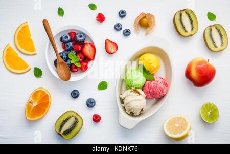 Colorful ice cream with mixed berry and various fruits raspberry ,blueberry ,strawberry ,orange ,kiwi ,apple,lemon - Stock Photo
