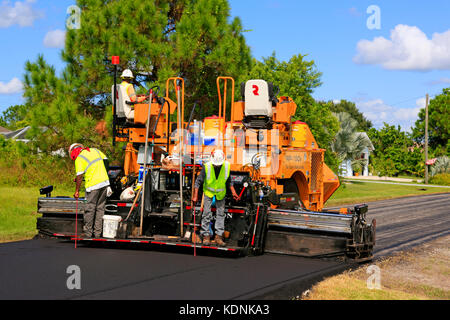Workers on an asphalt machine laying new roads in a residential neighborhood in Florida - Stock Photo