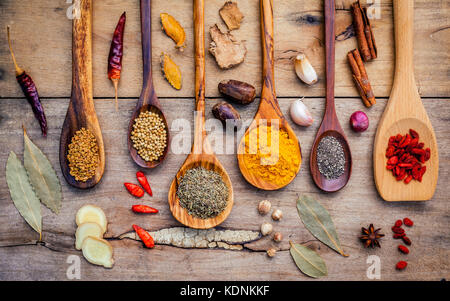 Various herbs and spices in wooden spoons. Flat lay of spices ingredients chilli ,pepper, garlic,dries thyme, cinnamon,star - Stock Photo