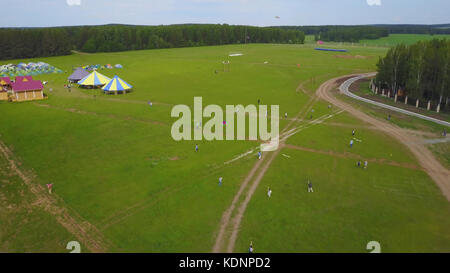 People flie a kite on grass in summer day. Group children flying kite outdoor. Flying kite in motion making loops - Stock Photo