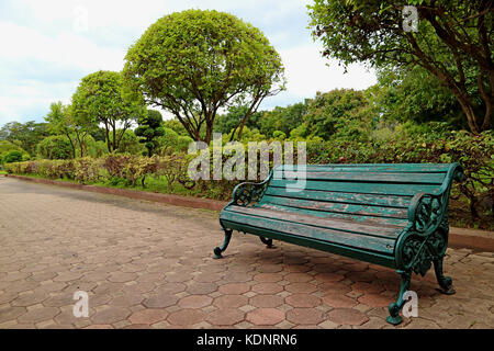 Green Colored Wood and Wrought Iron Bench on the Pathway in Public Garden of Thailand - Stock Photo
